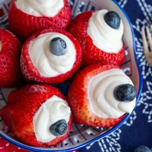 Bowl of strawberries stuffed with lemon cream cheese filling and topped with a blueberry.
