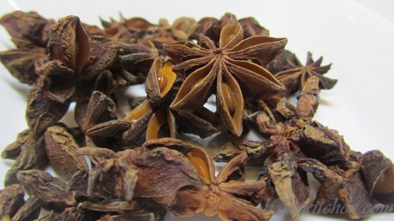 Pile of Star Anise on a white plate.