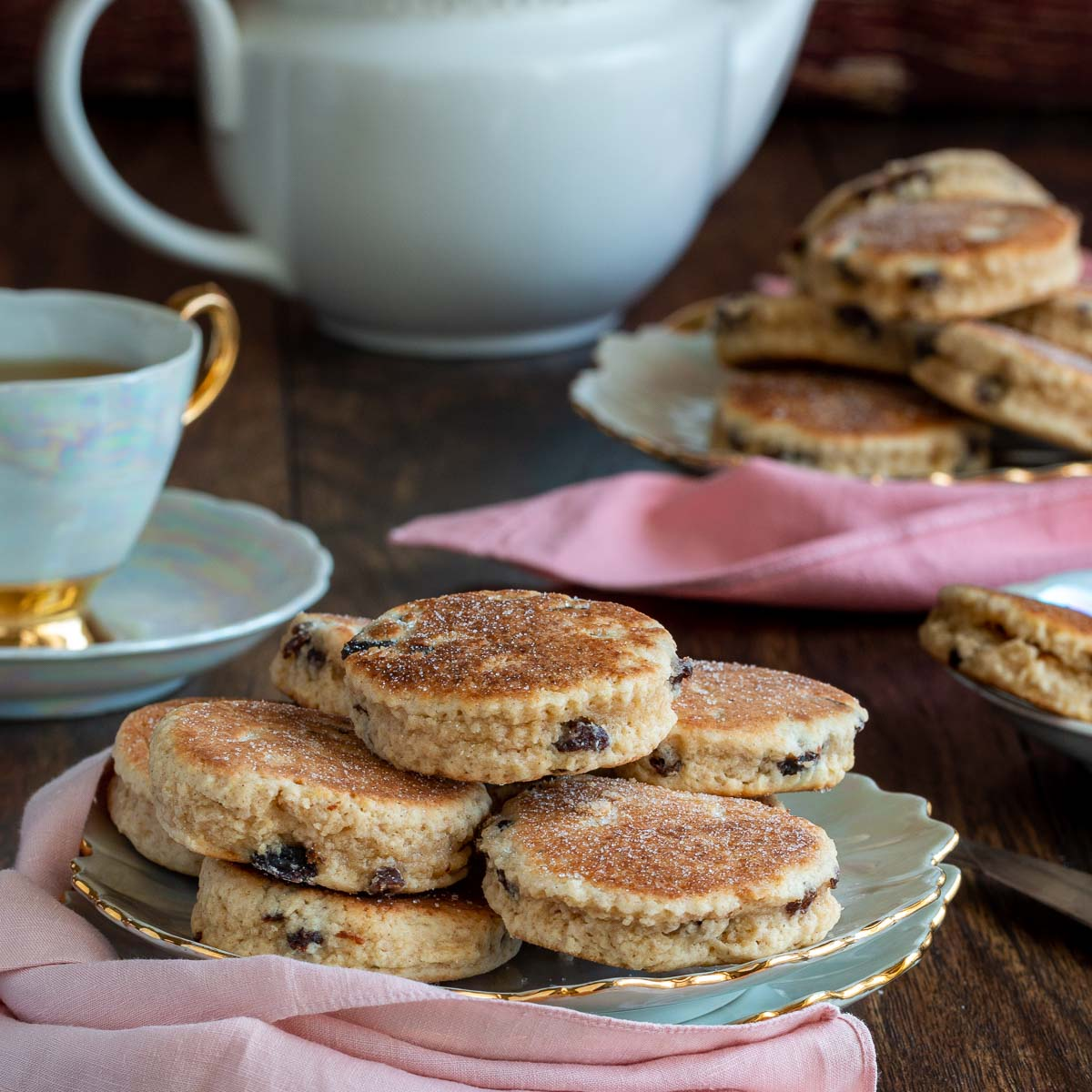 Dish of traditional welsh cakes in a pretty plate with matching tea set.