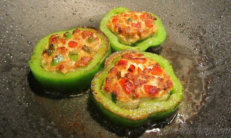 Pepper rings stuffed with pork mixture frying.