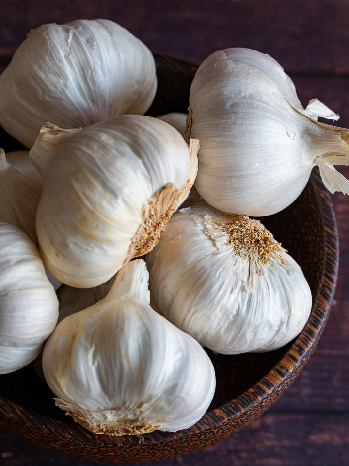 8 bulbs of garlic in a wooden bowl looking down into them with the soft light highlighting their white skin.