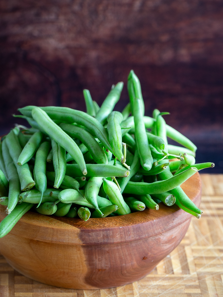 A cherry wooden bowl filled with about one pound of fresh green beans.