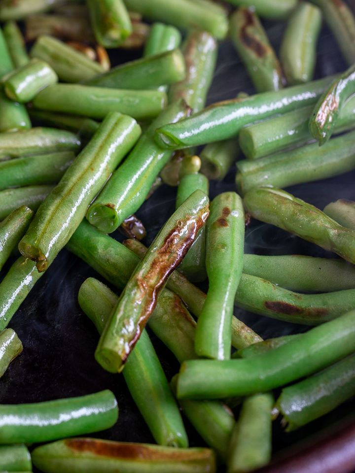 Green beans getting dry fried and seared in an iron skillet.