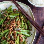 Stir fried dry fried green beans and minced pork in a Chinese bowl with wooden chop sticks and a side of rice.