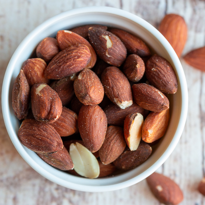 Toasted whole almonds in a white bowl.