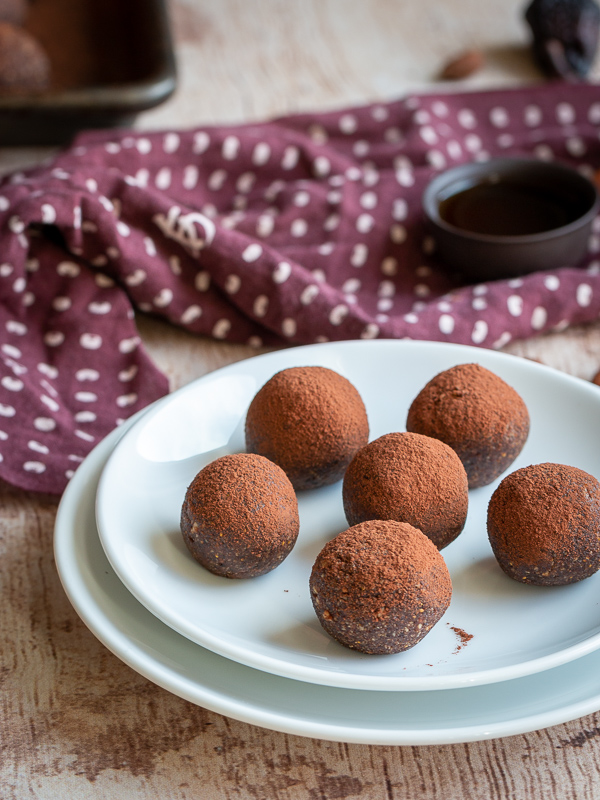 Plate of chocolate espresso fig balls with hot pu-erh tea and a brown napkin.