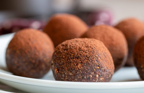 5 chocolate espresso balls on a white plate.