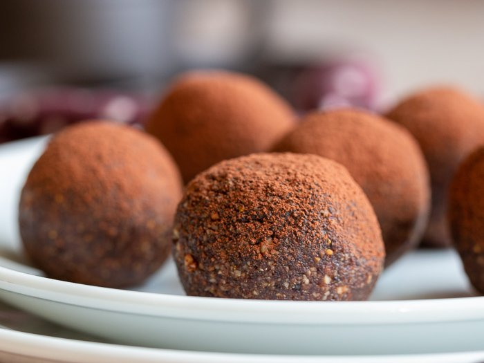 5 chocolate espresso balls on a white plate.