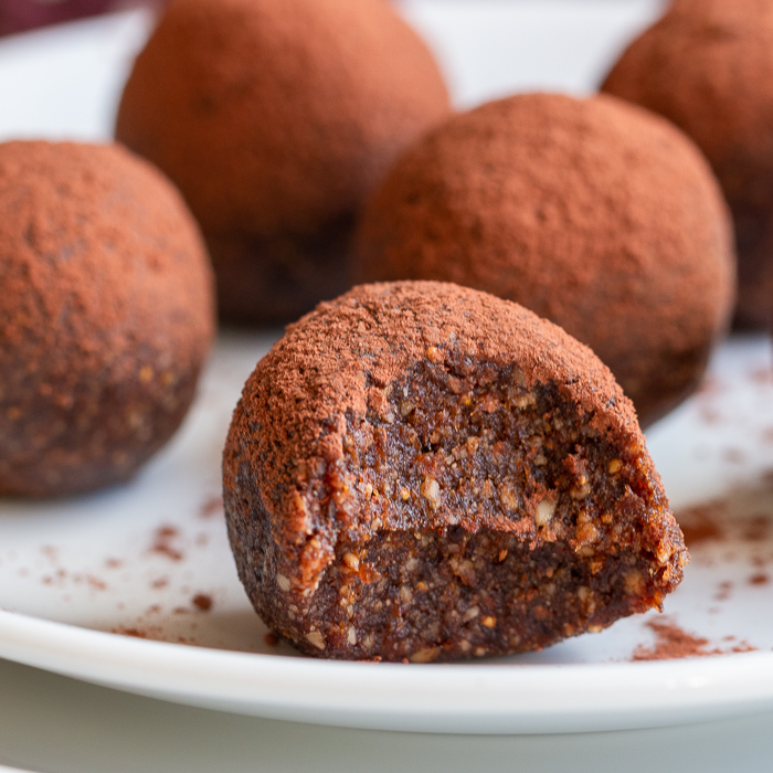 Plate of chocolate Espresso Fig Balls on a white plate with a but out of the one in the front.