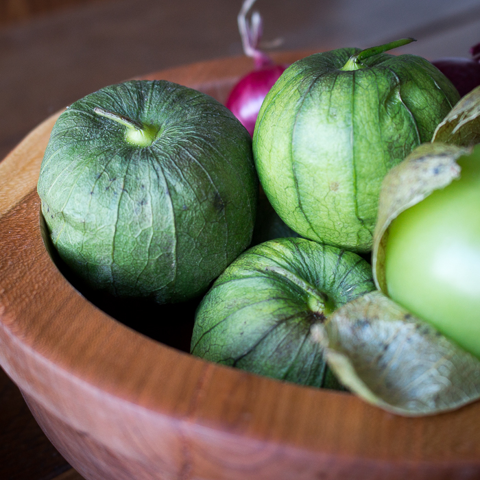 Close up of raw unpeeled tomatillos in a wooden bowl