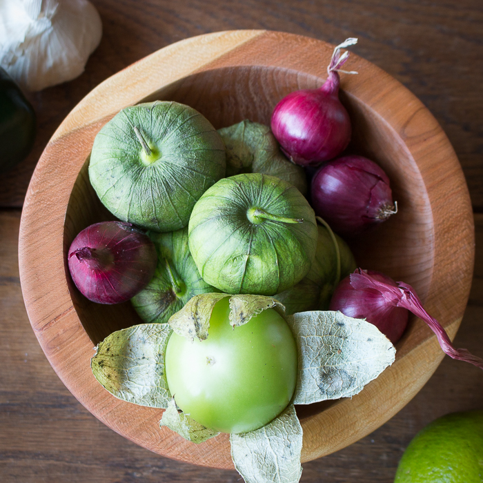 top down shot of tomatillos, onions, garlic to be roasted
