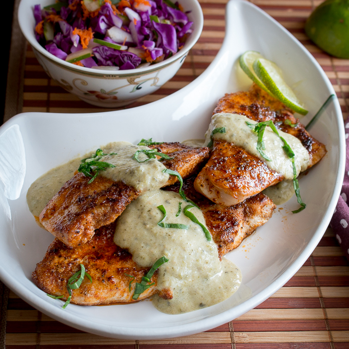 Top down photo of tomatillo salsa on chicken with a coleslaw