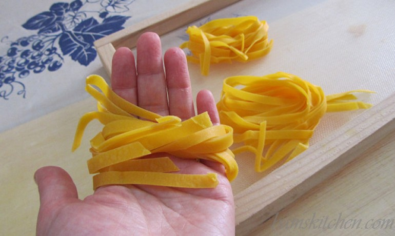 Tagliatelle noodles tossed around my hand to make a nest ready to be dried.
