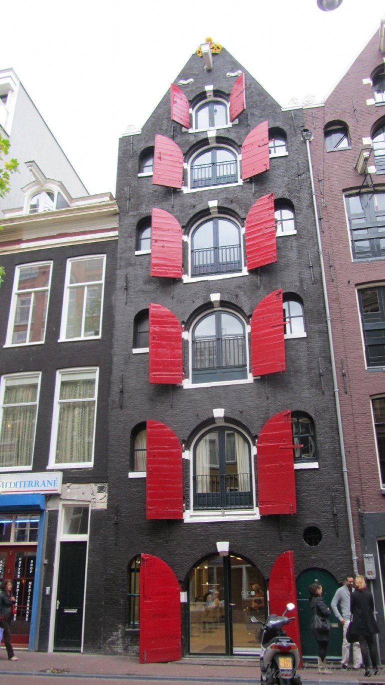 Amsterdam architecture with red shutters on the canal.