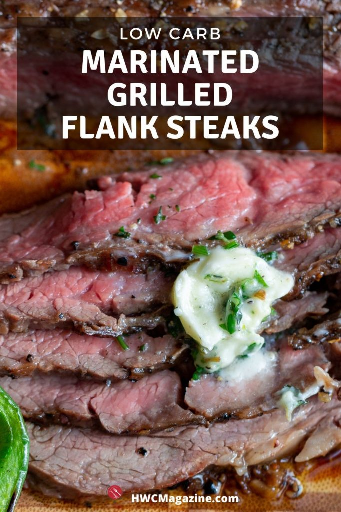Grilled flank steak cut into thin slices on a cutting board and garnished with herb butter and fresh herbs.