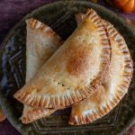 3 pumpkin hand pies on a green plate.