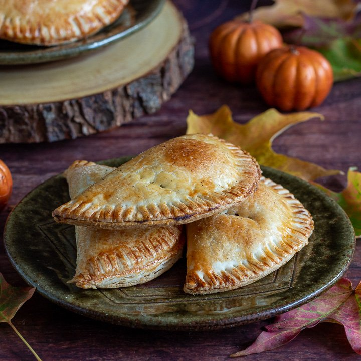 Fall scene with pumpkins, leaves and hand pies on a plate.