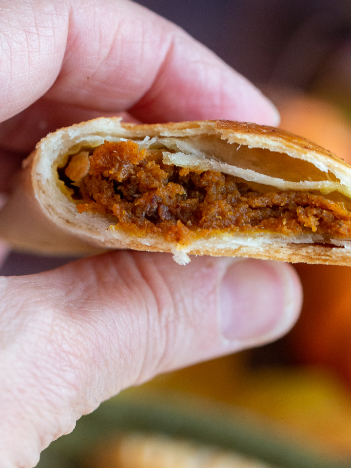 Pumpkin hand pie in a hand cut in half showing the delicious pumpkin filling and flaky crust.