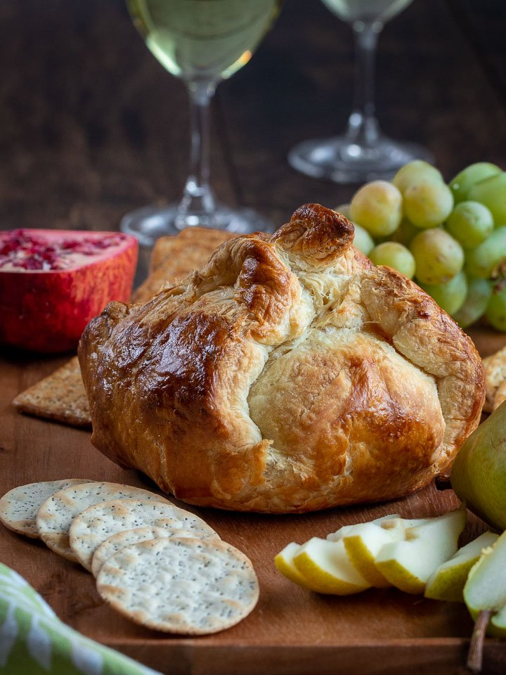 Whole savory baked brie in puff pastry just baked with crackers, wine and fruits to serve on side.
