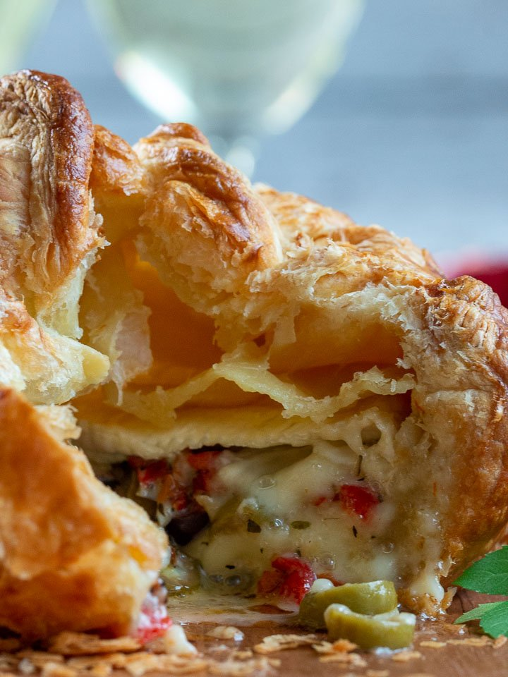 Baked brie en croute with a slice out showing the cheese oozing out.