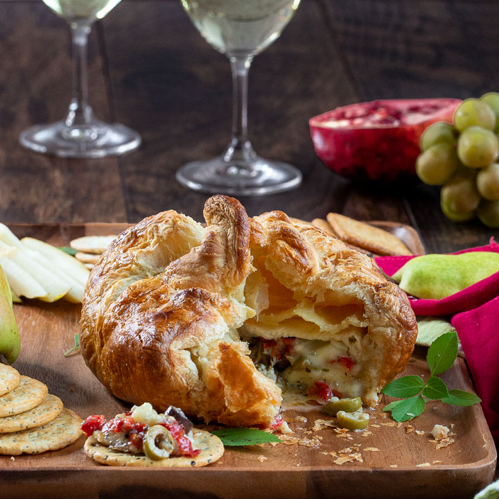 Savory Baked Brie in Puff Pastry on a cheese board cut open to show the melty cheese and Mediterranean ingredients inside.