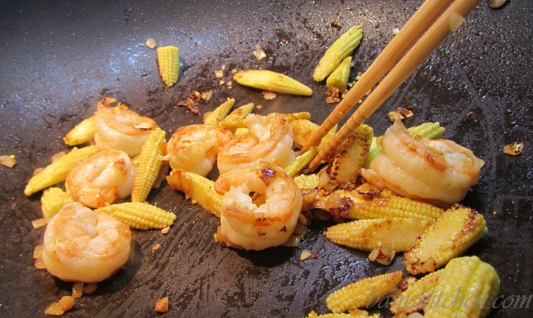 Shrimp and baby corn getting cooked in the wok with cooking chopsticks.