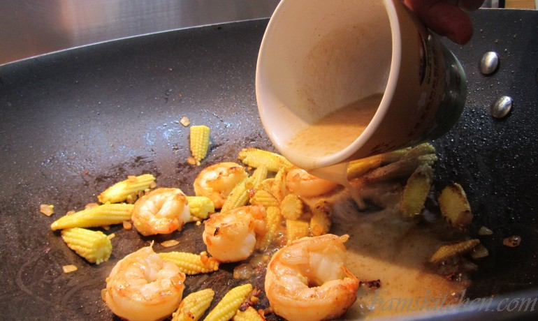 Cornstarch slurry getting added to the vegetables and shrimp in the wok.