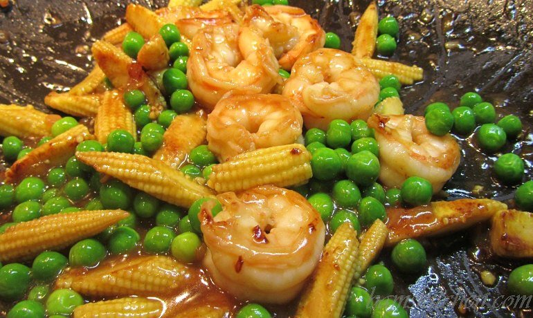 Veggies and shrimp in the wok with the delicious seasonings. Glossy and beautiful.