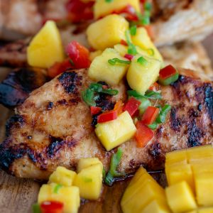 Grilled Mango chicken breasts topped with fresh mango salsa on a wooden board.