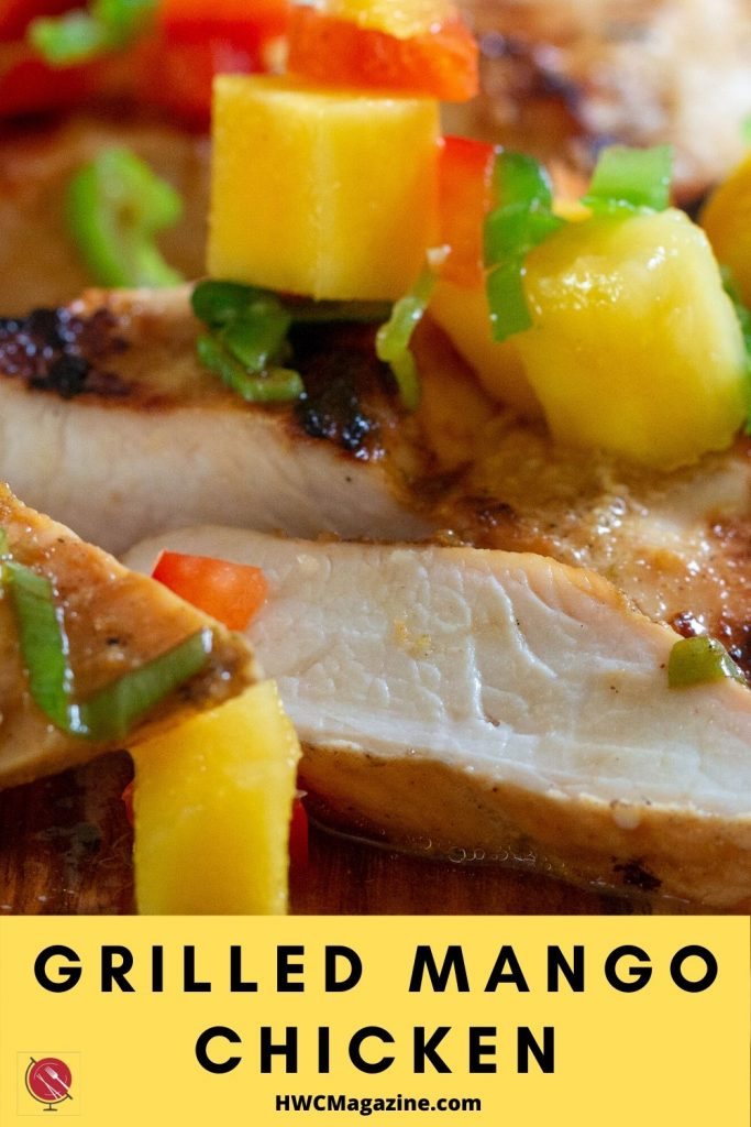 Grilled Mango chicken breasts topped with fresh mango salsa on a wooden board. Sliced juicy chicken.
