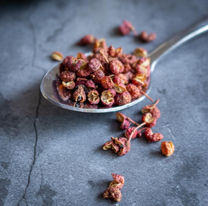 Sichuan peppercorns in a spoon.