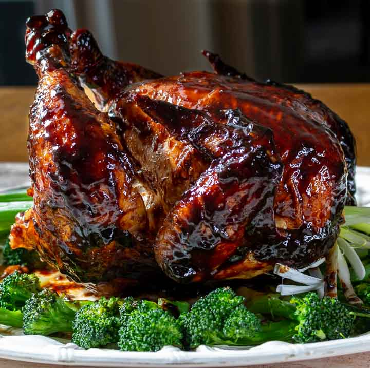 Perfectly grilled Peking style beer butt chicken on a white platter with vegetables around.