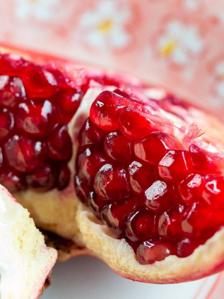 Close up shot of a fresh pomegranate cut into quarters.