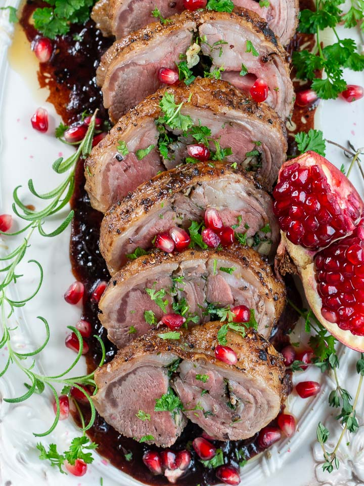 Top down shot of roasted lamb loin topped with pomegranate seeds and herbs.