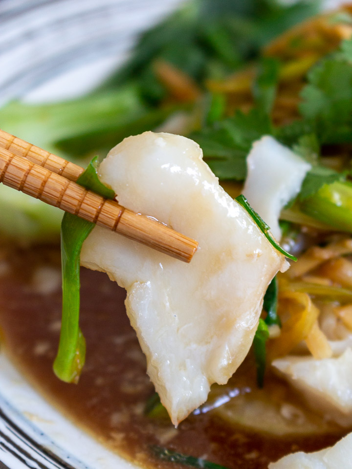 Bite shot of perfectly teamed cod held with chop sticks.