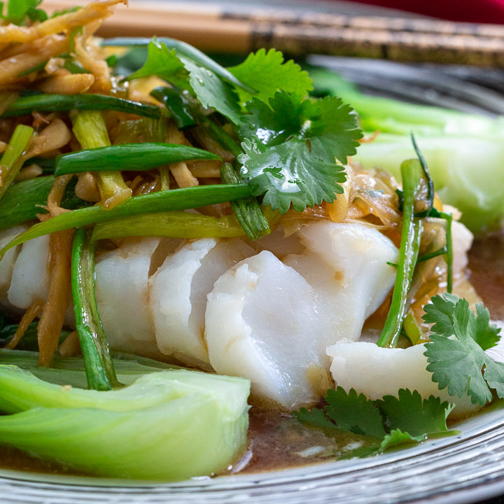 Close up shot of flaky Asian Steamed cod fish topped with Asian Sauce.