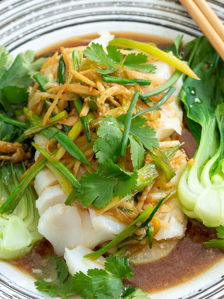 Plated Asian Steamed Fish garnished with fresh cilantro.