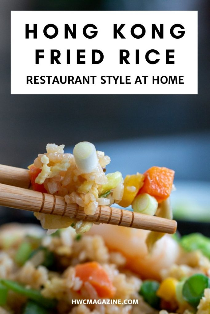 Fried rice getting scooped up with chopsticks.
