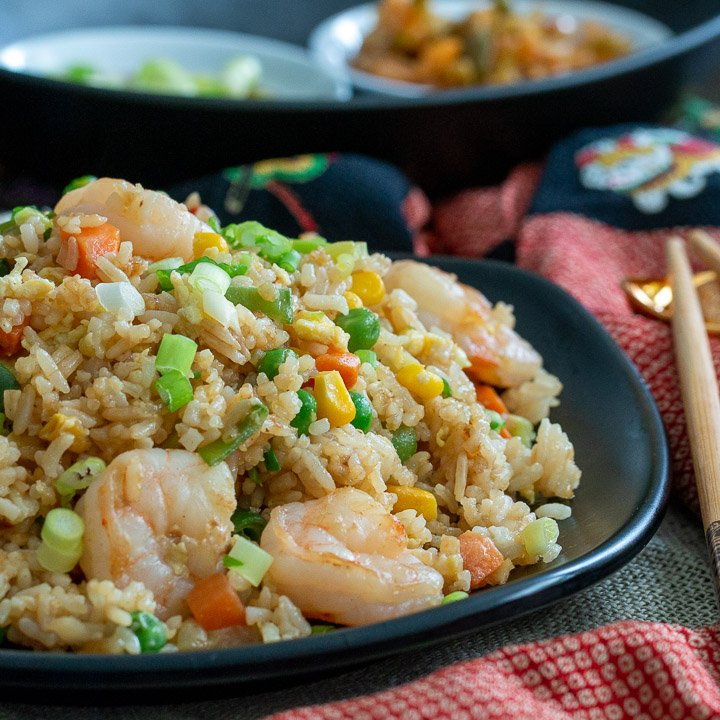 Resturant style Hong kong Fried rice with shrimp on a black plate with chopsticks.