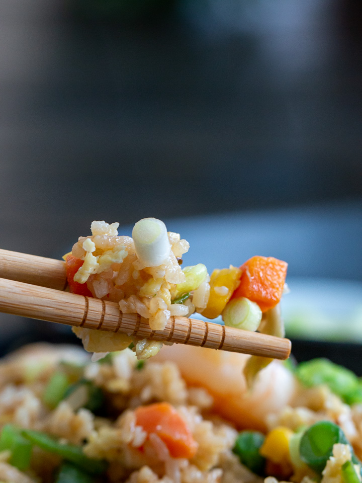 A bite shot showing the individual grains of rice, small vegetables and snow flakes of egg in the fried rice.