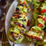 Grilled green chicken kabab in a white plate sprinkled with red chilis.