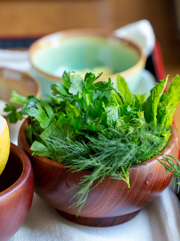 Fresh green herbs in a wooden bowl.