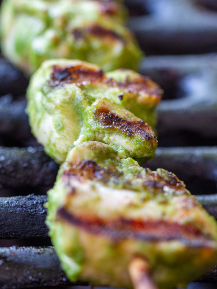 Close up shot of a green chicken kabab on the grill with delicious grill marks.