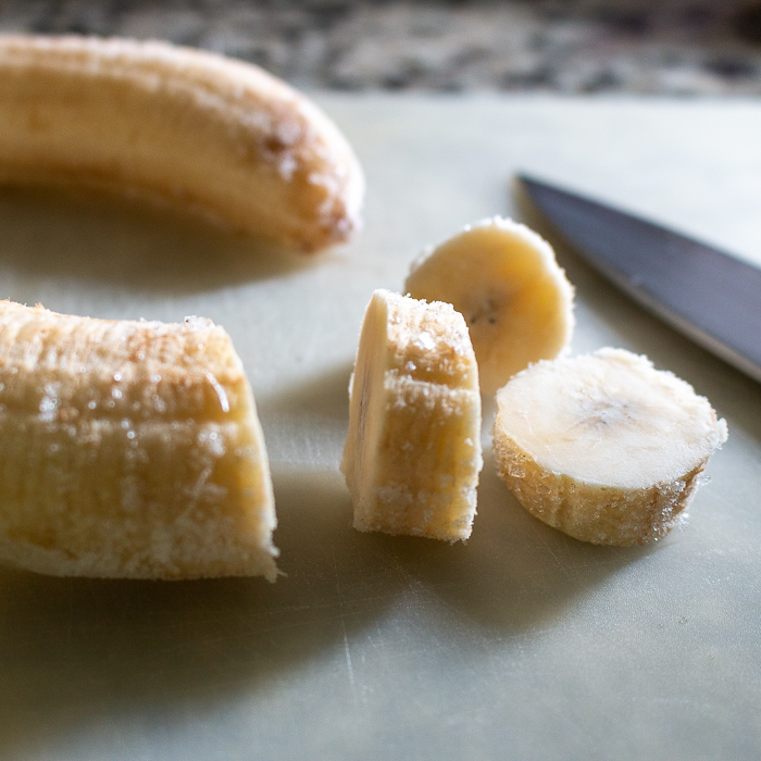 Frozen bananas chopped on a white cutting board with knife on cutting board.