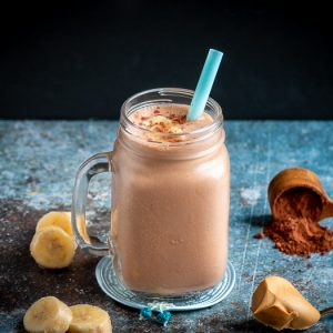 Creamy rich chocolate peanut butter smoothie topped with bananas and unsweetened chocolate cocoa powder. Surrounded by chopped bananas , peanut butter.