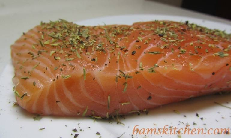 Salmon sprinkled with a little herbs de Provence ready to be cooked.