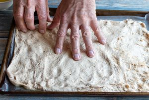 Spreading dough out in a baking sheet.