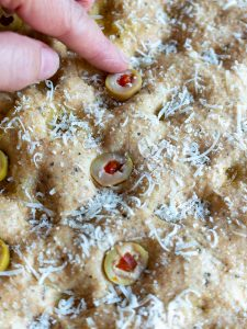 Adding olives to the dough.