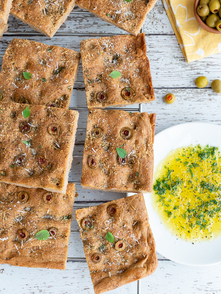 9 slices of focaccia bread with olives and herb dipping oil.