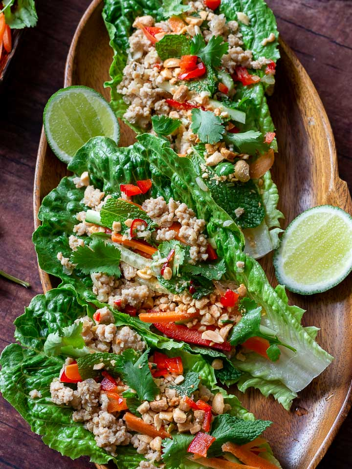 Healthy Chicken Lettuce wraps all prepared with toppings and ready to be served on a wooden Thai platter.